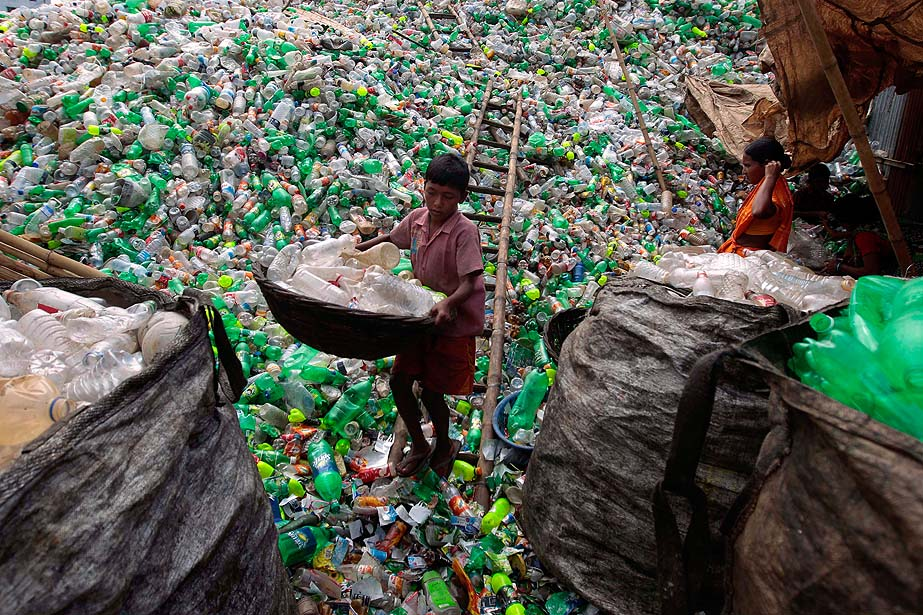 A Bangladeshi child laborer carries empty bottles at a plastic bottle recycling center in Dhaka, Bangladesh, Tuesday, Sept. 18, 2012. (AP Photo/A.M. Ahad)
